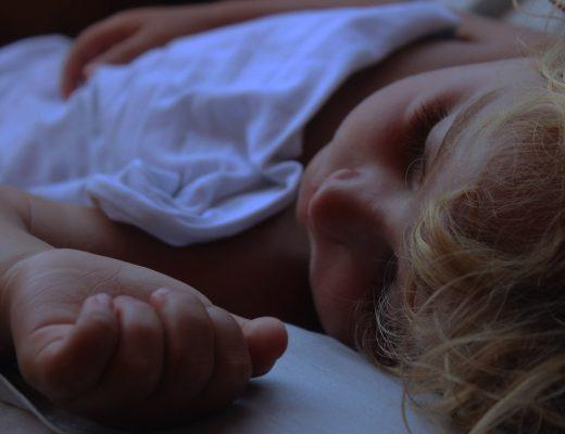 Niño durmiendo plácidamente arropado por un edredón nórdico. Ángulo normal desde la cabeza del niño con un plano detalle que muestra el rostro, el edredón nórdico y una mano del niño.