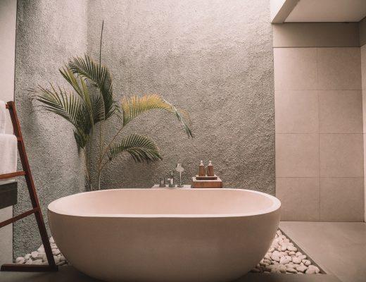 Bañera ovalada de mármol beige con diseño minimalista. La acompaña una palmera. La estancia donde está colocada es minimalista con tonos beige y grises.