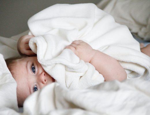 Bebé sonriendo tapado con unas sábanas de coralina