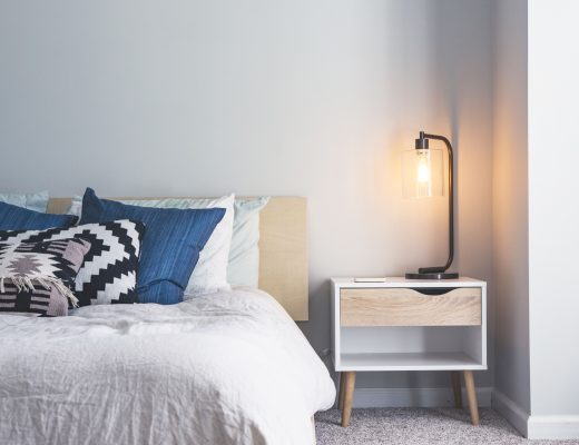 Visualización de una cama vestida con una colcha bouti de verano en color blanco. La pared es de color gris claro. La habitación tiene un toque minimalista con muebles color madera combinado con blanco.