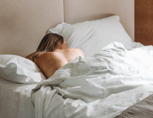 Edredón nórdico blanco que envuelve a una mujer mientras duerme