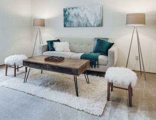Salón en tonos neutros como blanco, beiges y grisáceos combinados con muebles rústicos y de madera natural. El sofá también es de color gris claro y los cojines decorativos de un verde azulado intenso.