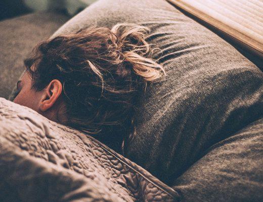 Vista semi aérea de mujer durmiendo sobre sábanas de coralina y microlina tapada con un edredón nórdico