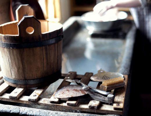 cubo de madera y utensilios antiguos para quitar las manchas de los tejidos