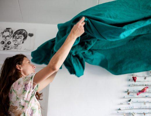 Mujer alzando en el aire las sábanas de Burrito Blanco