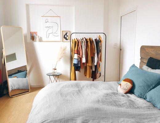 Dormitorio moderno con edredón nórdico reversible en tono gris y cojines en tonos azules y mostaza