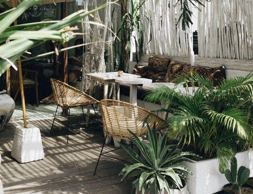 Terrazas veraniega con cojines de exterior, paredes de ramas blancas de madera, elementos naturales y palmeras