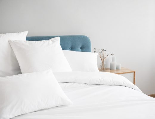 Cama con sábanas blancas y almohadas blancas.