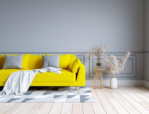 Vista frontal de salón con sofá amarillo Pantone y pared gris combinando suelo de madera gris claro y alfombra geométrica en tonos grises