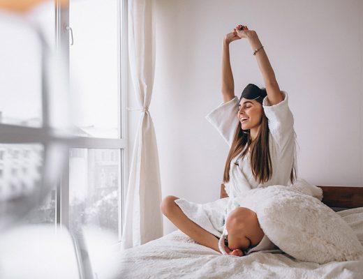 Sabanas de verano. Mujer despertándose sobre cama con sábanas blancas de verano.