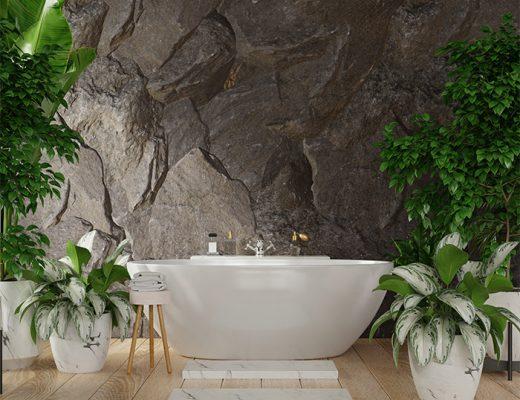 Baño moderno. Bañera blanca rodeada de plantas y taburete de madera frente a pared natural de piedra