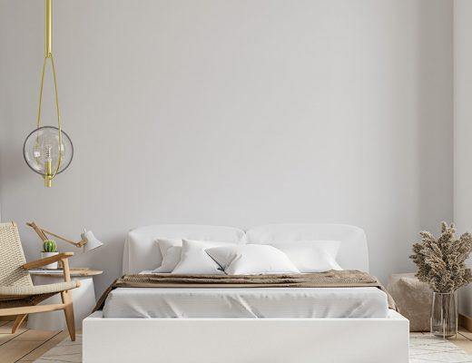 Dormitorio luminoso en tonos beige y madera. Sabanas blancas combinadas con manta marrón y cojines blancos